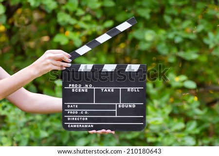 Movie clapper board in hands outdoors - stock photo