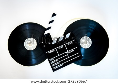 Movie clapper board on two 35 mm film reels linked with filmstrip on neutral background - stock photo