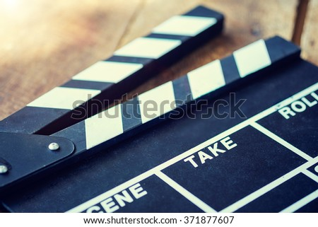 Movie clapper on wood table.vintage effect - stock photo