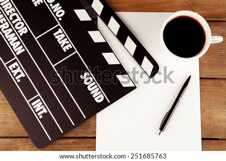 Movie clapper with paper, pen and cup of coffee on wooden planks background - stock photo