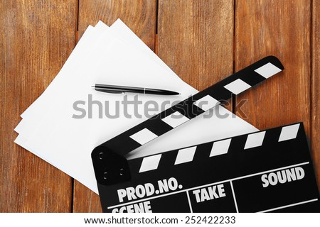 Movie clapper with sheets of paper and pen on wooden planks background - stock photo