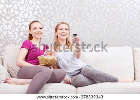 Movie night. Two young beautiful girls sitting on a white couch watching a movie while holding remote control and eating popcorn at pajama party full length  - stock photo