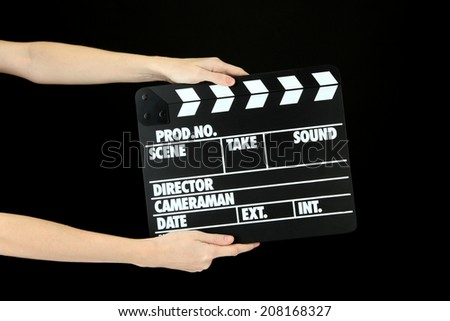 Movie production clapper board isolated on black - stock photo
