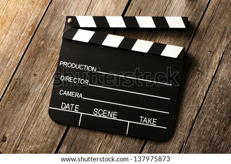 Movie production clapper board over wooden background - stock photo