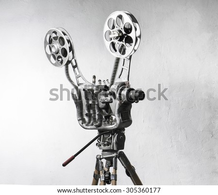 Movie projector with the film on the background of gray wall - stock photo