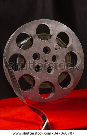 Movie reel on a red table and black background - stock photo