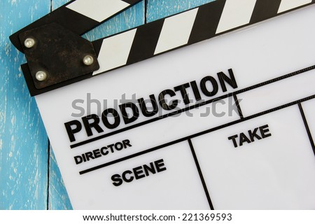 Movie slate film on blue wooden table - stock photo