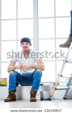 Moving and repairs in the apartment. Smiling painter sitting on a windowsill and holding a brush in his hand while his friend standing in the background on a ladder in an empty apartment - stock photo