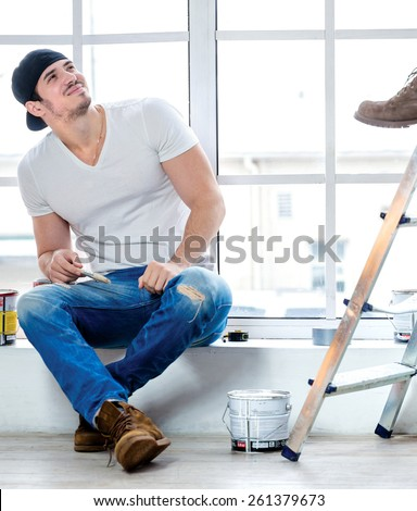 Moving and repairs in the apartment. Young painter man sitting on a window sill and looking up while his friend standing in the background on a ladder in an empty apartment - stock photo
