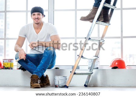 Moving and repairs in the apartment. Young worker guy sitting on a windowsill and holding a brush with paint in his hands while his friend standing in the background on a ladder in an empty apartment - stock photo