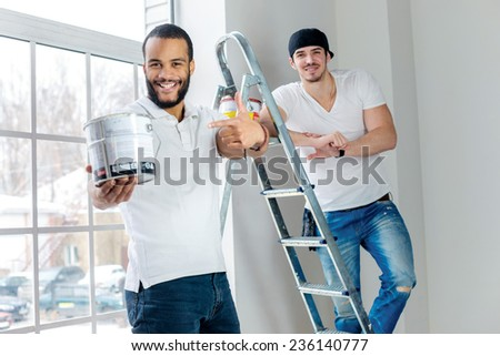 Moving and repairs in the apartment. Young worker man holding a paint can and showing a thumbs up while his friend standing in the background on a ladder in an empty apartment - stock photo