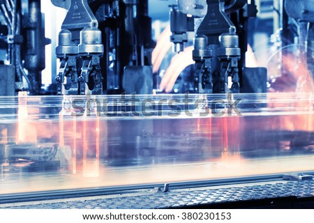 Moving assembly line for production of bottles toned in blue - stock photo
