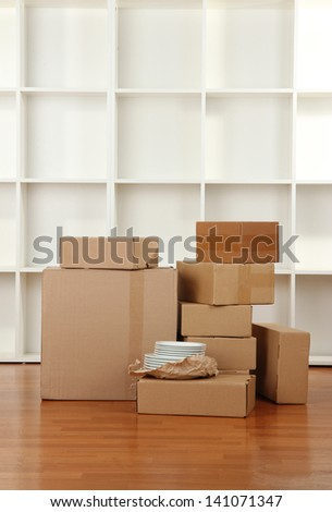 Moving boxes in empty room - stock photo