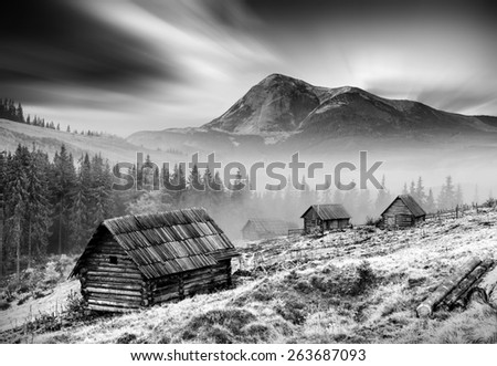 Moving clouds above high mountain misty valley with old wooden houses on a hill. The Goverla, higher mountain of Ukraine, on a skyline. Monochrome colors - stock photo