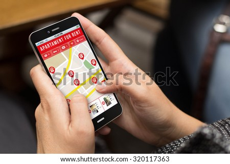 moving concept: girl using a digital generated phone with apartment search website on the screen. All screen graphics are made up. - stock photo