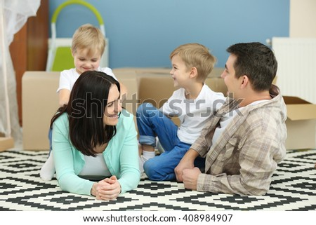 Moving concept. Happy family lying on carpet with cardboard boxes in new house - stock photo