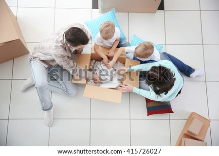 Moving concept. Happy family unpacking boxes in new house, top view - stock photo