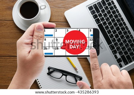 MOVING DAY! message on hand holding to touch a phone, top view, table computer coffee and book - stock photo