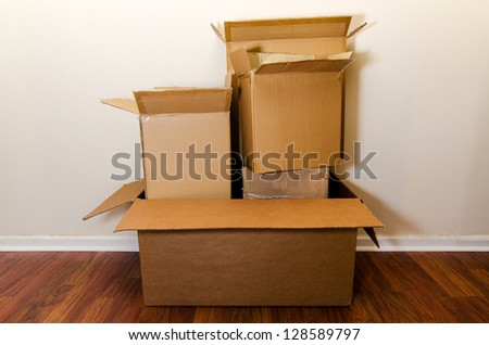 Moving day with empty cardboard boxes on hardwood floor. - stock photo