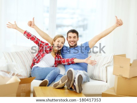 moving, home and couple concept - smiling couple relaxing on sofa in new home - stock photo