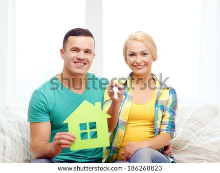 moving, home and couple concept - smiling couple with green house and keys in new home - stock photo
