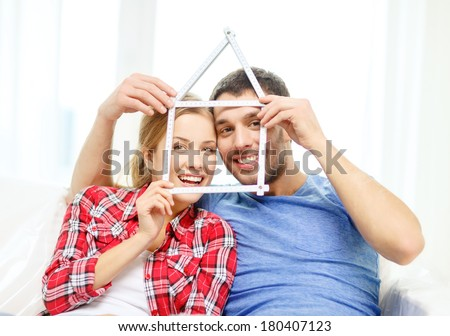moving, home and couple concept - smiling couple with house from measuring tape at new home - stock photo
