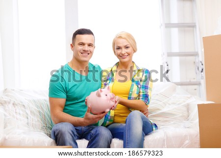 moving, home and couple concept - smiling couple with piggybank in new home - stock photo