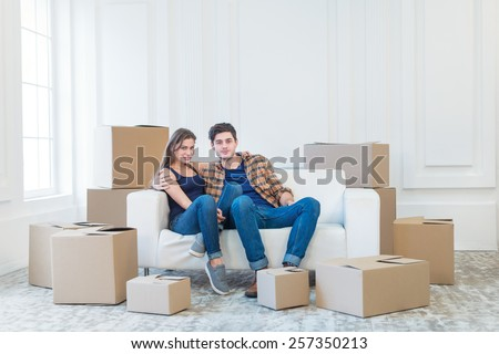 Moving home and relocation of a new life. Couple in love pulls things out of boxes for moving while man and woman sitting among the boxes in an empty apartment - stock photo