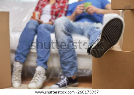 moving, home, repair and people concept - close up of couple legs relaxing and sitting on sofa with cups in new apartment - stock photo