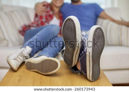 moving, home, repair and people concept - close up of couple legs relaxing and sitting on sofa with legs on table in new apartment - stock photo