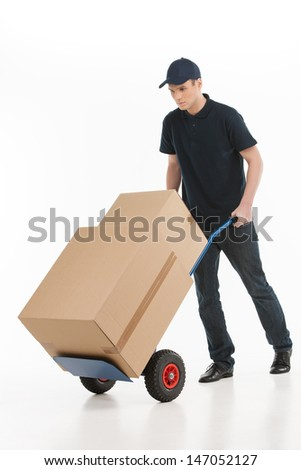 Moving house. Full length of young deliveryman with a hand truck transporting the cardboard boxes - stock photo