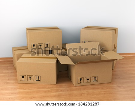 Moving in concept: group of cardboard boxes in empty room - stock photo