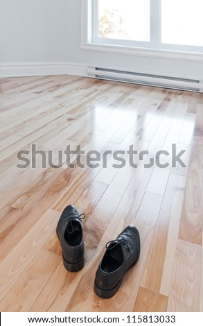 Moving in. Shoes entering an empty room full of light. - stock photo
