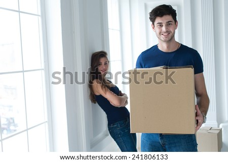 Moving new flat with fun and excitement. Portrait of young and handsome man moving to new apartment surrounded with plenty of cardboard boxes. His beautiful wife is on the background - stock photo
