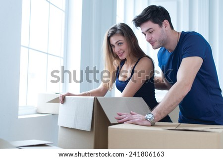 Moving new flat with fun and excitement. Young and beautiful couple is moving to new apartment surrounded with plenty of cardboard boxes. Both are opening boxes with smiles - stock photo