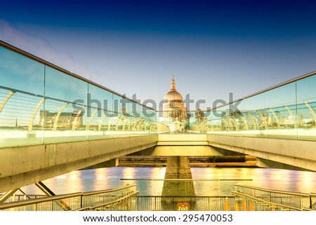 Moving people alonf Millennium Bridge in London. Night view of St Paul Cathedral. - stock photo