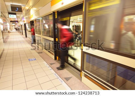 moving people leaving train at a metro railway station, shot in Taipei, Taiwan, asia - stock photo