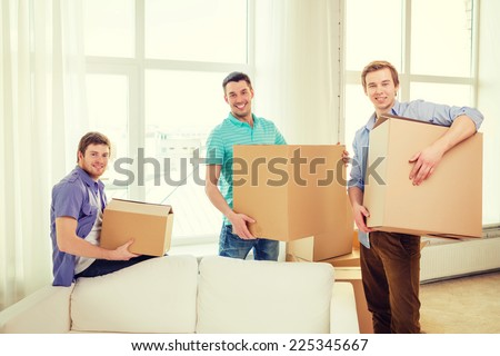 moving, real estate and friendship concept - smiling male friends carrying boxes at new place - stock photo