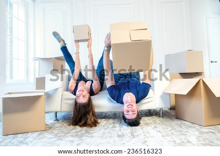 Moving, repairs, new apartment. Couple girl and the guy keep moving boxes in hands and looking at the camera while man and woman lying on the sofa among the boxes in an empty apartment - stock photo