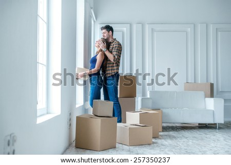 Moving, repairs, new life. Couple in love enjoys a new apartment and keep the box in his hands while young man close her wife eyes in an empty apartment among boxes - stock photo
