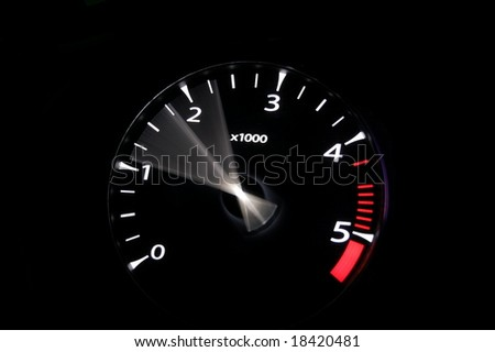 moving revs meter of a sports car on a black background. - stock photo
