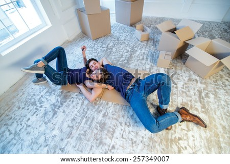 Moving, shifting, repairs, new home. Couple girl and guy lie on the floor in an embrace while man and woman lying on the floor among the boxes in an empty apartment - stock photo