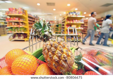 Moving shopping cart in supermarket. It was taken from the shopper's point of view. - stock photo