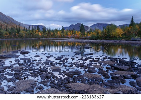 Moving skies above a northern taiga forest reflected in shallow freshwater Polygonal lake in Hibiny mountains above the Arctic Circle - stock photo