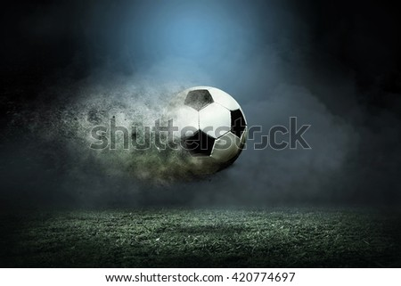 Moving soccer ball around splash drops on the stadium field. - stock photo