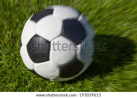 moving soccer ball on green field - stock photo