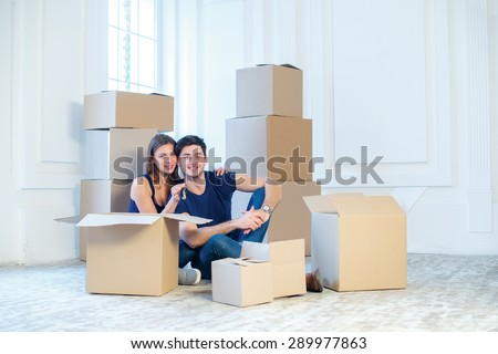 Moving to a new house and repairs in the apartment. Love couple sitting on a couch and hugging while a young and beautiful couple in love sitting in an empty apartment among boxes - stock photo