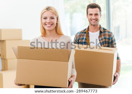 Moving to a new house together. Cheerful young couple holding cardboard boxes while other carton boxes laying on background - stock photo