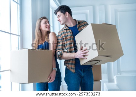 Moving to a new life. A girl and a guy holding boxes for moving the hands and looking at each other while a couple in love standing at the window among boxes - stock photo