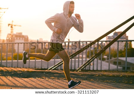 Moving to his goal. Side view of confident young man running along the bridge - stock photo